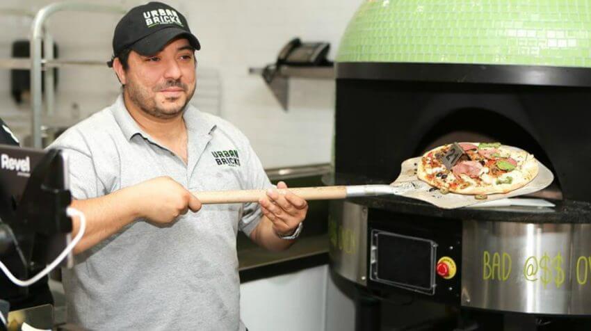 Urban Brick chef in front of Marra Forni rotator brick oven