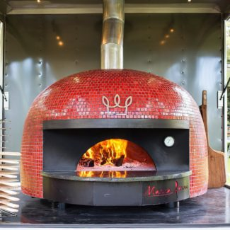 red tiled mobile brick oven with metal big bon logo next to pizza peels