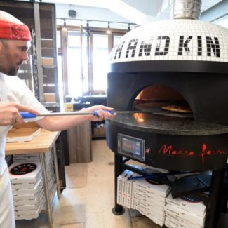Pizzaiolo spins pizza inside white tiled marra forni oven in pizzeria