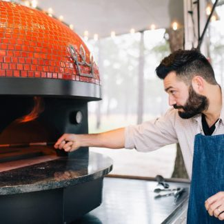 Italian Chef spins pizza inside red mobile pizza brick oven