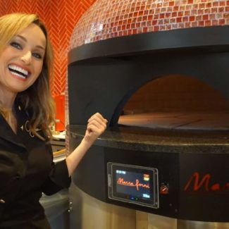 Giada De Laurentiis happily stands and points to red rotator brick oven from marra forni