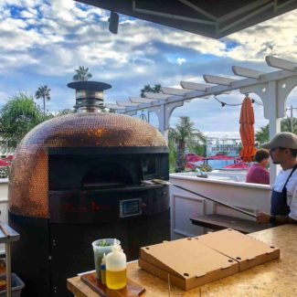Golden brick pizza oven next to beautiful blue sky