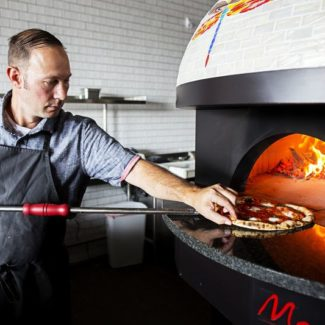 Chef taking pizza out of inferno pizzeria brick oven