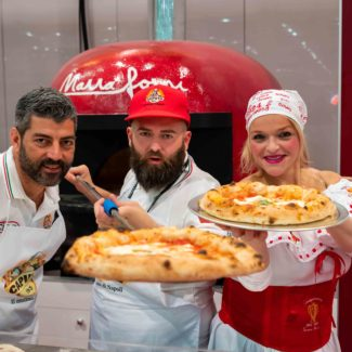 Caputo team shows off pizza in red marra forni oven