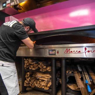 Bright pink marra forni bagel oven with fresh wood beneath