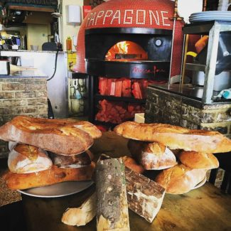 Pappagone neapolitan brick oven with fresh baked breads in front