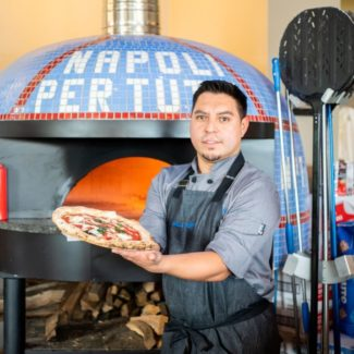 Chef from Napoli Pertuto holding pizza in front of neapolitan marra forni brick oven