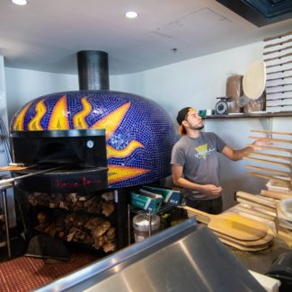 Pizza maker tosses pizza in Pizzeria Paradiso by bright purple and yellow brick oven
