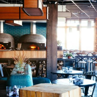 Tazza Kitchen two brown tiled wood fired ovens in open restaurant