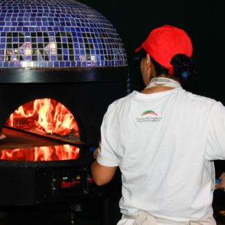 Wood Fired Brick Oven baking pizza at night