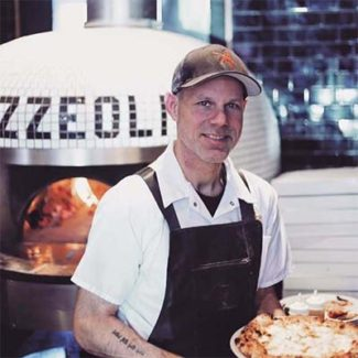 Chef holding pizza infront of brick oven inscribed with Pizzeoli